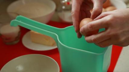 Baking cake. Hands separating egg into bowl