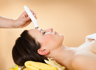 Woman Receiving Microdermabrasion Therapy On Forehead At Spa