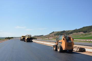 carretera con asfalto reciente y maquinaria de construccion