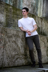 Handsome young man against stone blocks, looking away