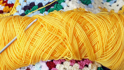 Skein of yarn in bright yellow with crochet hook