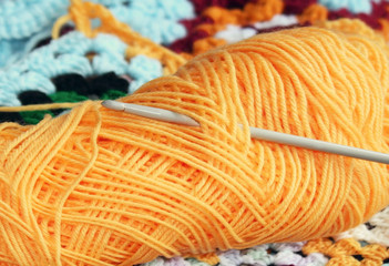 Skein of yarn in yellow gold with crochet hook