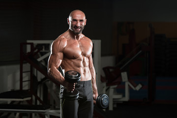 Mature Bodybuilder Exercising Biceps With Dumbbell