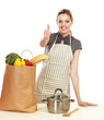 Woman in apron standing with grocery bagand showing ok