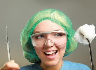 Portrait of young woman doctor surgeon (or nurse) with scalpel