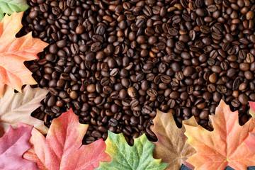 Kaffeebohnen mit bunten Herbstblättern umrandet