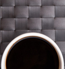 A mug of black coffee on a woven place mat