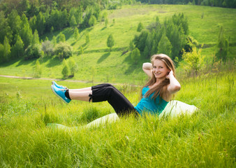fitness girl training sit up outside in grass in summer.