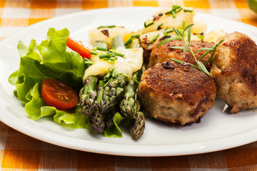 Meatballs served with boiled potatoes and asparagus