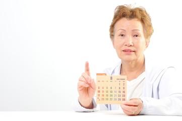 カレンダーを持つシニアの日本人女性