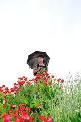 日傘を差して花の咲く道をあるく女性