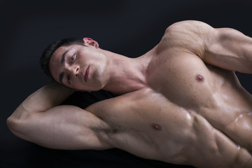 Attractive young man on the floor with muscular ripped body