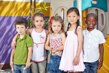 Kinder in multikultureller Gruppe im Kindergarten