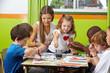 Leinwanddruck Bild - Kinder malen mit Erzieher im Kindergarten