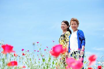 花の咲く道を歩く母親と娘