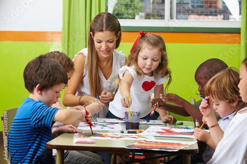 canvas print picture Kinder malen mit Erzieher im Kindergarten