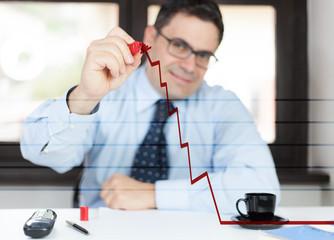 Uomo in ufficio disegna un grafico in salita