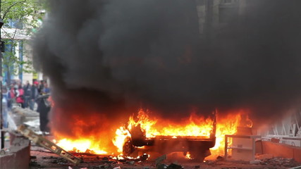 Burning car in the center of city during unrest
