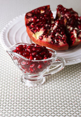 Ripe pomegranate on plate,  on light background