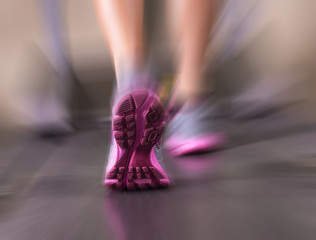 Runner feet running in fitness room closeup on shoe.