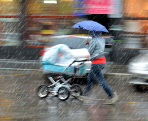 Mother walks with the child in the stroller on a rainy day