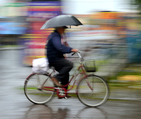 Cyclist in motion riding down the street on rainy day