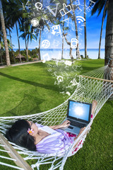 Asian tourist lying on net using laptop at beach