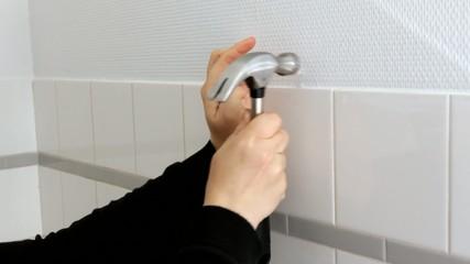 Hammering a nail into wall