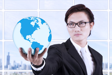 Businessman hold globe in hand - indoor