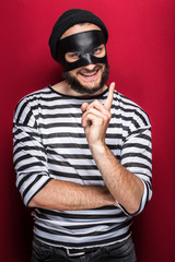 Crafty bandit smiling and threaten with finger on red background