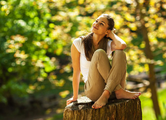 Young attractive woman sitting and relaxing  in park.