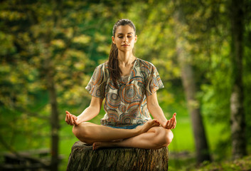 Young female meditate in nature.
