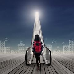 College student stepping upward on escalator 1