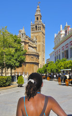 young woman looks at the La Giralda Tower in Seville - Spain