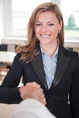 Sympathische Geschäftsfrau begrüßt und schüttelt Hand