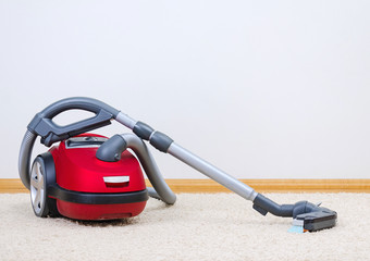 Red vacuum cleaner in empty room.