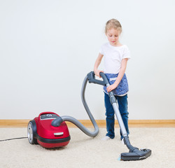 Cute little girl cleaning carpet with vacuum cleaner.