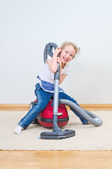 Cute little girl having fun during house cleaning.