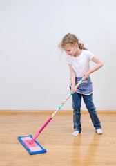 Little cute girl mopping floor at home.