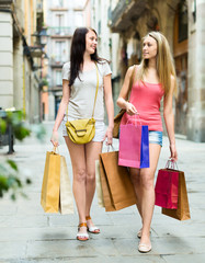 Two girls walking with shopping