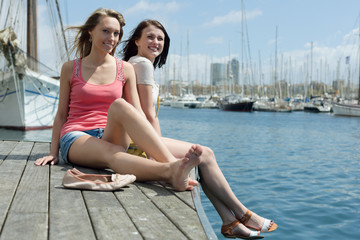 Two girls students enjoying sunny day on the sea