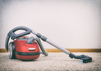 Red vacuum cleaner in empty room. Photo with vignette.