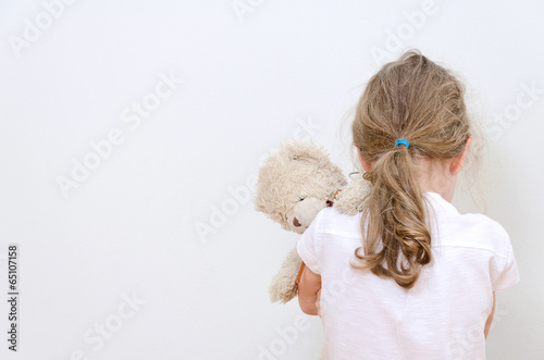 Little girl crying in the corner. Domestic violence concept. - 65107158