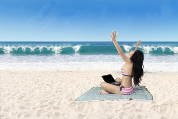 Successful woman working with laptop at beach