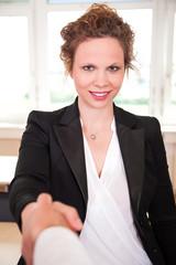 Junge Geschäftsfrau schüttelt freundlich Hand bei Empfang