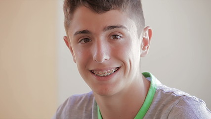 Teenager with dental appliance smiling and looking at camera