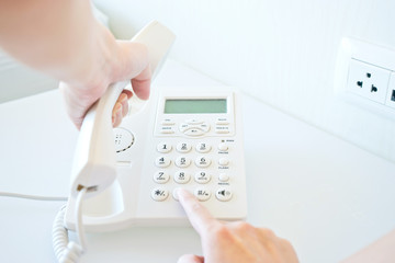 Photo of female hands dialing on white telephone