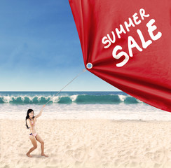 Woman pulling a banner of summer sale 1
