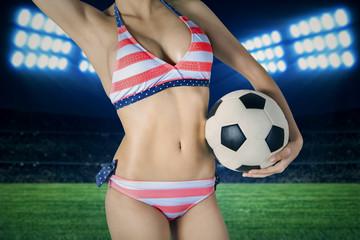 Woman wearing bikini with a ball on field