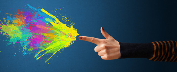 Colorful splashes are coming out of gun shaped hands